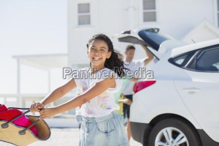 happy girl swinging beach bag outside
