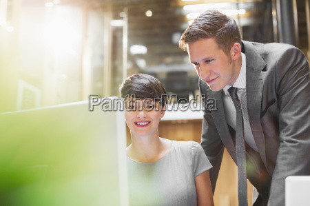businessman and businesswoman using computer in