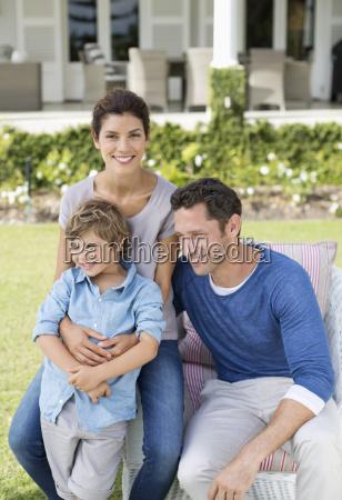 family smiling outside house