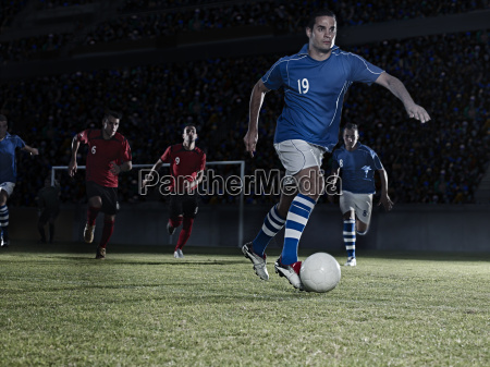 soccer players chasing ball on field