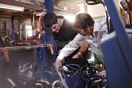 mechanics working on car in auto