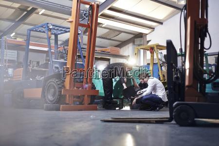 mechanics working near forklift in auto
