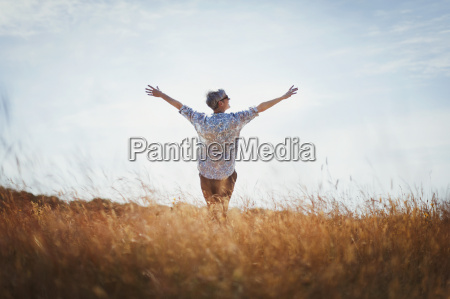 exuberant senior woman with arms outstretched