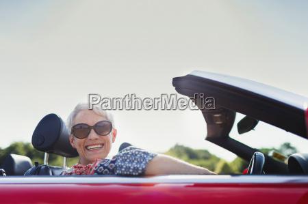 portrait senior woman driving convertible