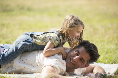 playful daughter laying on top of