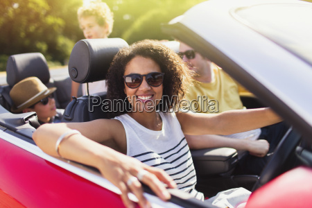 portrait enthusiastic woman driving convertible with