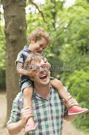playful son covering fathers eyes in