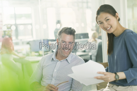 portrait smiling business people reviewing paperwork