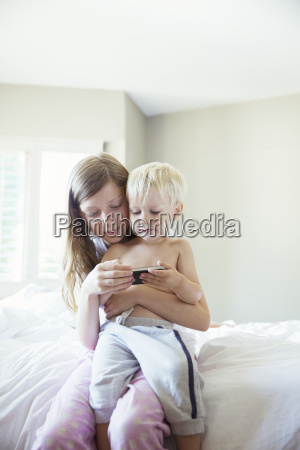 children using cell phone together on