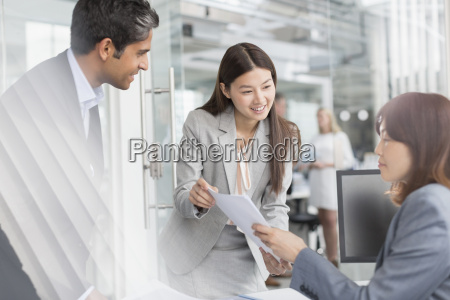 business people discussing paperwork in office