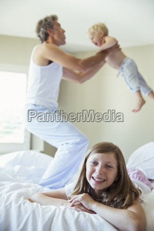 father and children playing on bed