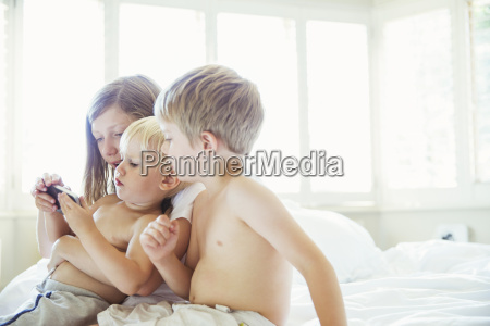children using cell phone on bed