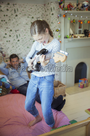 girl playing guitar for father in