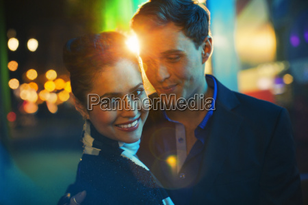 couple hugging on city street at