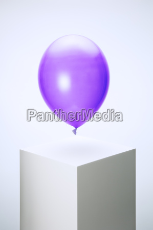 purple balloon hovering over pedestal