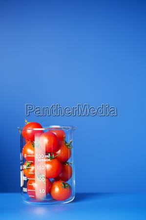 beaker of small tomatoes on blue