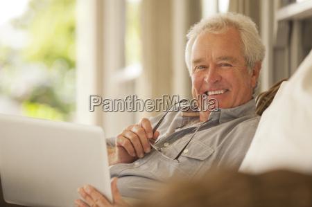 portrait of smiling senior man using