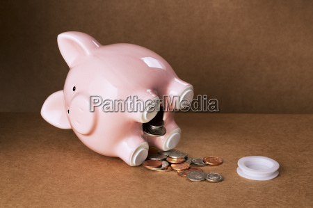 piggy bank spilling out change onto