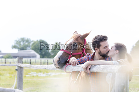 couple with horse kissing at rural