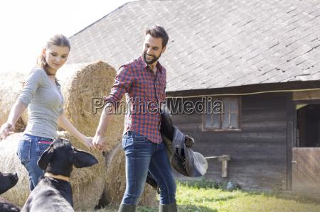 couple holding hands walking with saddle