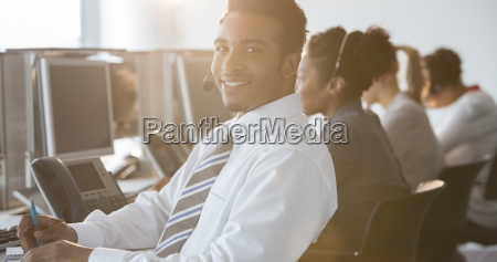 businessman with headset smiling in office