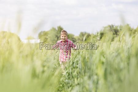 carefree boy running in sunny rural