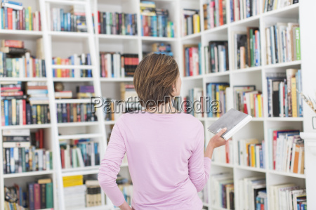woman selecting book from library