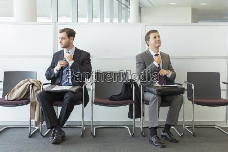businessmen adjusting ties in waiting area
