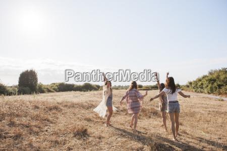 carefree boho women dancing in sunny