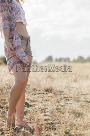 boho woman standing in sunny rural