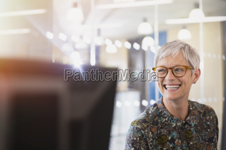 enthusiastic senior businesswoman looking away in