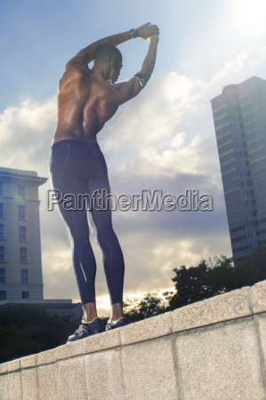 man stretching before exercising on city