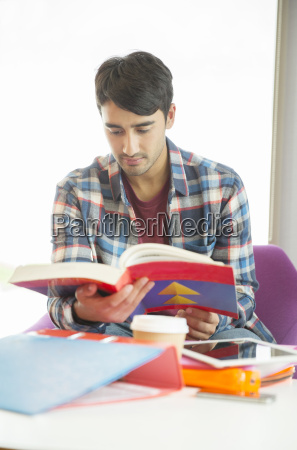university student reading textbook in lounge