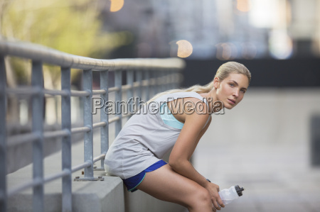 woman resting after exercising on city