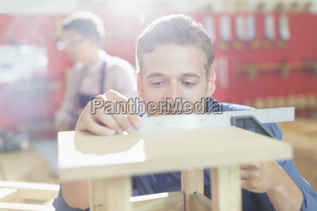carpenter measuring wood with ruler in
