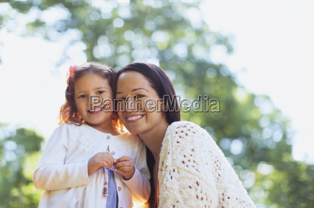 portrait smiling mother and daughter outdoors