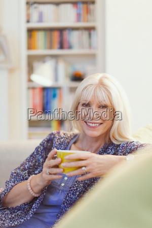 portrait smiling senior woman drinking coffee