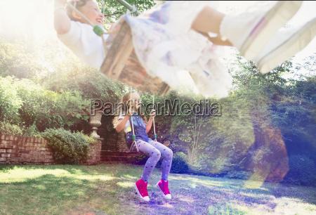 girls swinging in backyard