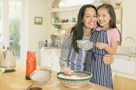portrait playful mother and daughter baking