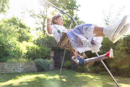 carefree girls swinging in backyard