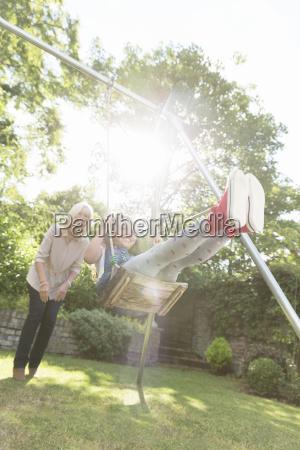 grandmother pushing carefree granddaughter on swing