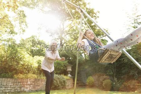 grandmother pushing granddaughter on swing in