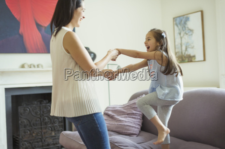 playful mother and daughter dancing in