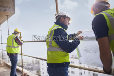 construction worker and engineer reviewing blueprints