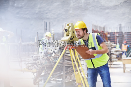 engineer with clipboard using theodolite at