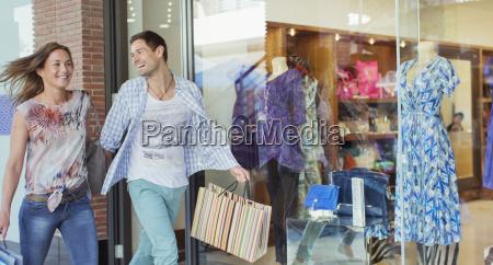 couple carrying shopping bags in shopping