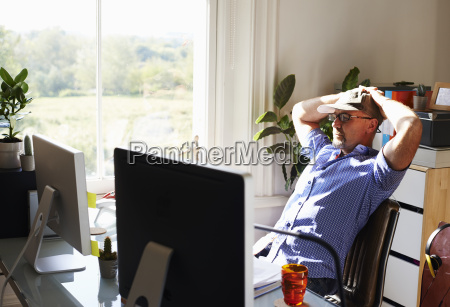 man leaning back working at computer