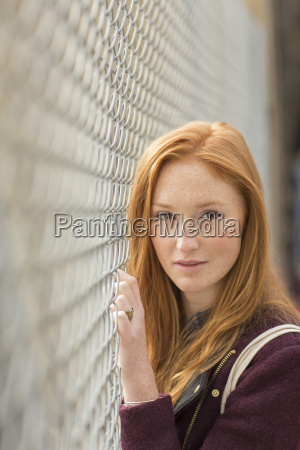 woman standing at chain link fence