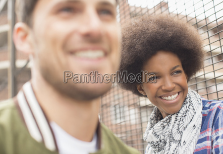 man and woman smiling near fence