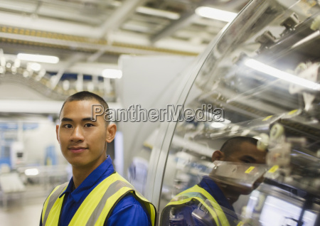 portrait confident worker leaning on machinery